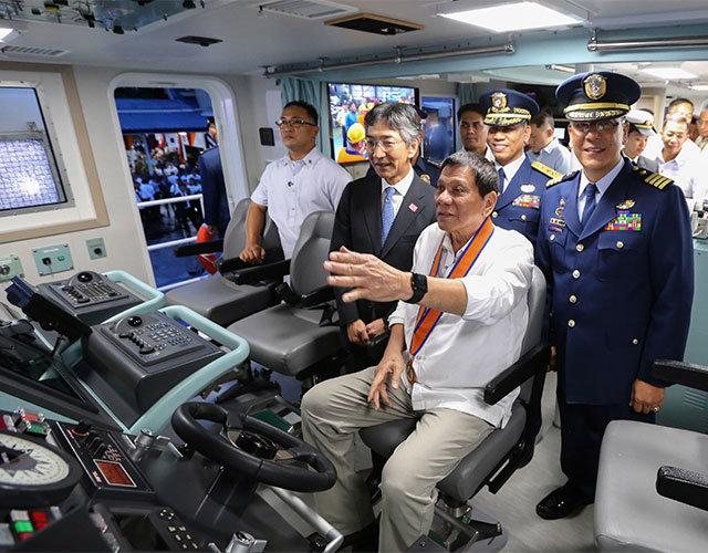 tong thong philippines rodrigo duterte ngoi vao ghe thuyen truong tren tau tuan duyen moi do nhat cung cap - anh: afp